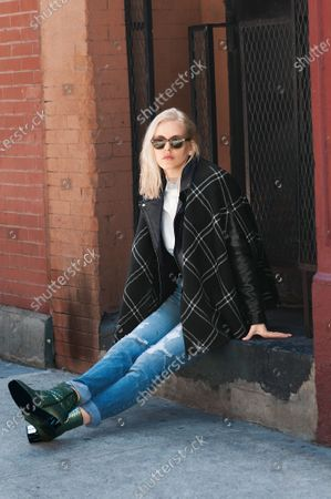 Stock Image of Designer Lindsey Butler wearing a plaid wool cape by Ralph Lauren with Moscot sunglasses, leather moto jacket, button-down shirt by Surface to Air, green snakeskin boots by Dries Van Noten and vintage Levi ripped jeans. Lindsey Butler