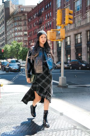 Stock Image of Designer Jen Kao wearing a beanie from Arth, a Jen Kao vinyl jacket, Jen Kao green-stained wooden clutch bag and Chanel military boots. Jen Kao