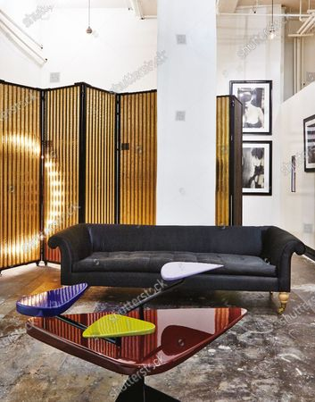 Stock Image of A Blackman Cruz Workshop screen, Clarke & Reilly sofa and a Vincent Darre table in front of the dressing area of Just One Eye boutique.