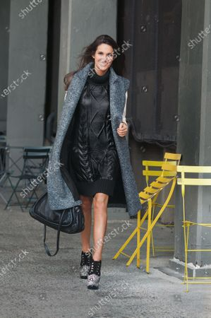 Stock Picture of Savannah Engel, Barneys New York public relations coordinator, wearing Tommy Hilfiger leather coated turtleneck dress with sleeveless Lanvin coat, Celine white shirt, and Celine Paraty purse and speckled pony-hair Alaia heels.