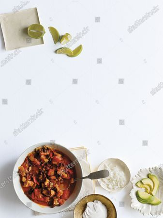 Overhead view of Turkey Chili with lime wedges and avocado slices.