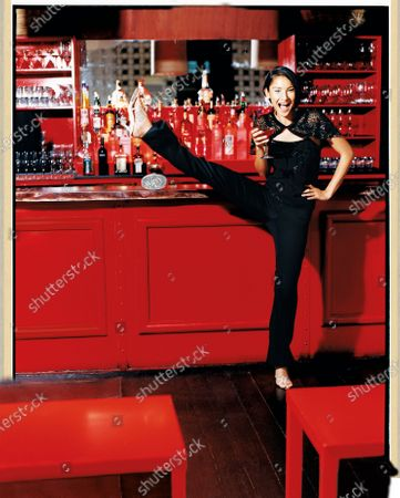 A woman holding a drink and wearing all black at PM Lounge in New York City's meatpacking district kicks up one leg over the red bar. Let loose in tuxedo pants. Add a demure capelet; its drapey sleeves instantly slenderize arms. Pants, Express Design Studio. Capelet, and camisole, Banana Republic. Shoes, Manolo Blahnik. Earrings, Roxanne Assoulin for Lee Angel. Crystal clutch, Moo Roo.