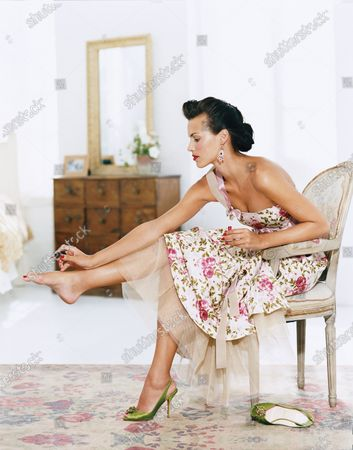 Stock Photo of A woman in a one shouldered rose floral dress with a tulle underskirt paints her toenails while seated. Don't let party prep stress you out. Use it as an excuse to treat your feet. No time for a pedicure? Simply soothe your soles by soaking them in cool water while doing your makeup, then polish. If you're a fan of bold color, use ridge filler as a base coat to keep from staining nails, says Deborah Lippmann, a manicurist and creator of the Lippmann Collection in New York City. Dress, Luisa Beccaria.