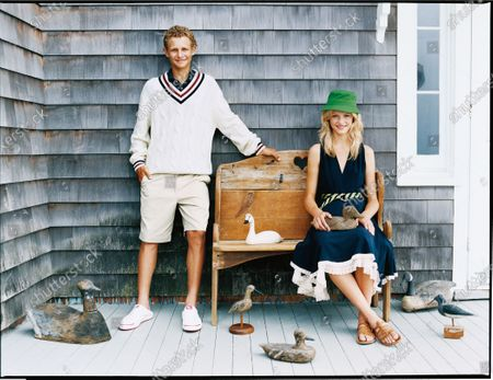 Preppy, seaside style: Model Ginta Lapina, wearing a navy blue Brett Lally for Borne dress and green Lacoste bucket hat, and Warren Elgort wearing a knit Bobby Jones  sweater with shorts, outside a New England shingle style house in The Hamptons. Ginta Lapina, Warren Elgort