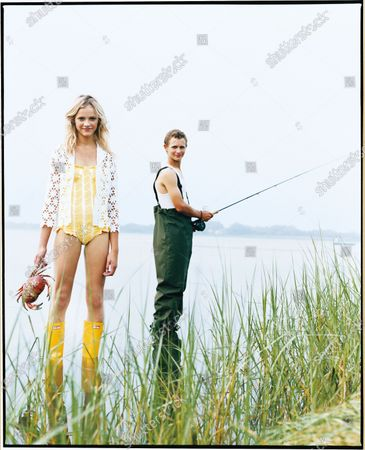 Woman in a crocheted white blouse over a white and yellow swimsuit and yellow Hunter boots holds a grab, while a man fishing in the background looks on. Lilly Pulitzer blouse over an Abaeté bathing suit. Ginta Lapina, Warren Elgort