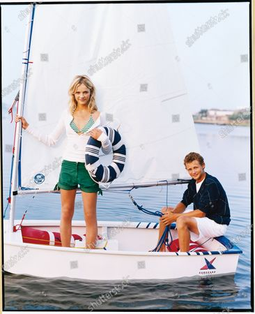 A woman in a striped bikini top, green shorts and a white henley stands on a sailing boat with a man in a navy sweater and white shorts. Abercrombie & Fitch henley, XOXO bikini top, Jill Stuart shorts. Ginta Lapina, Warren Elgort