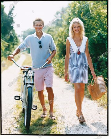 Woman in a blue and white striped dress with a wicker tote walks with a man rolling a bicycle in seersucker shorts and a blue sweater down a lane. Debra Rodman dress, A.P.C. necklace. Ginta Lapina, Warren Elgort