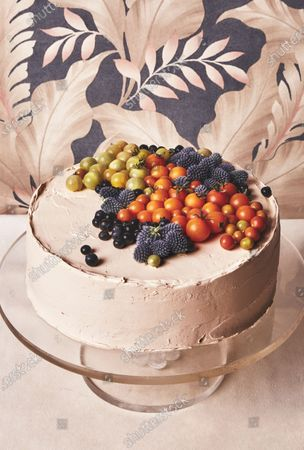 Tiramisù layer cake frosted with mascarpone mousse and decorated with blue thistle, blueberries, and cherry tomatoes. (.