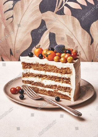 A slice of tiramisù layer cake with mascarpone mousse, decorated with blue thistle, blueberries, and cherry tomatoes.