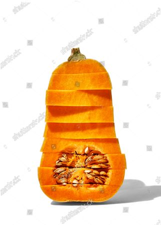 Cross-section view of a raw butternut squash sliced vertically and horizontally.