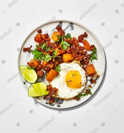 Plate of butternut squash and chorizo hash topped with cilantro leaves and served with a fried, sunny-side up egg and lime wedges.
