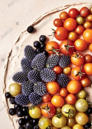 Blue thistles, blueberries, and cherry tomatoes on frosting as cake decorations.
