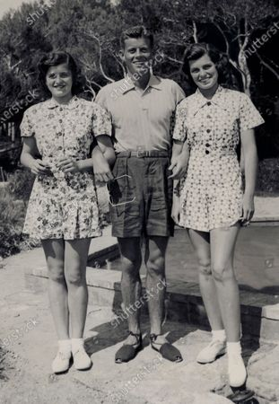 Stock Image of Eunice (wearing shorts-suit), Jack (wearing shorts and espadrilles), and Patricia (wearing shorts-suit) Kennedy, poolside at the American Embassy in London. Eunice Kennedy Shriver, John F. Kennedy, Patricia Kennedy
