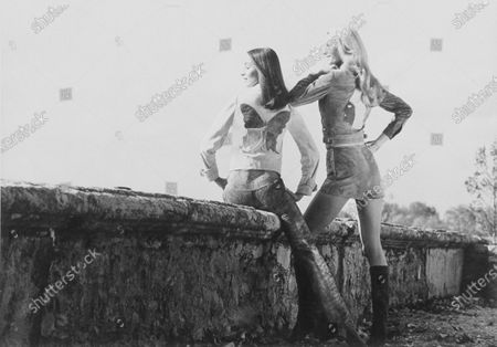 Canadian ballerina Sheron Rathscheck, left, wearing leather vest with butterfly appliqué by Daniel Hechter, with lambskin trousers by MacDouglas, and Diane de Monbrison wearing suede shorts and shirt with Indian-head appliqué, by Daniel Hechter, both wear boots by Maud Frizon, and are at La Chartreuse de Bonpas near Avignon. Sheron Rathscheck