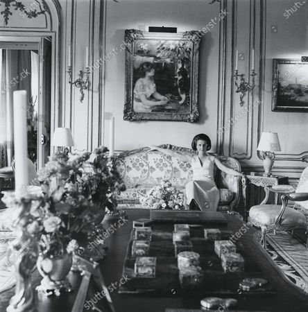 Stock Picture of Mrs. Charles (Jayne) Wrightsman wearing satin gown by Givenchy, sitting on a Louis XV cut-velvet sofa (signed by Pothier) under Renoir's Girl with Cat, ebony Louis XV table signed B.V.R.B. (made for Mme de Pompadour, owned later by the Duc de Richelieu) topped with a collection of rare snuff boxes. Jayne Wrightsman, Mrs. Charles Wrightsman