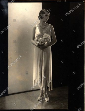 Actress Josephine L. Laimbeer wearing white satin evening dress with deep decolletage, natural waist, and asymmetrically hemmed skirt with tiny pleats; designed by Yvonne Carette. Josephine L. Laimbeer