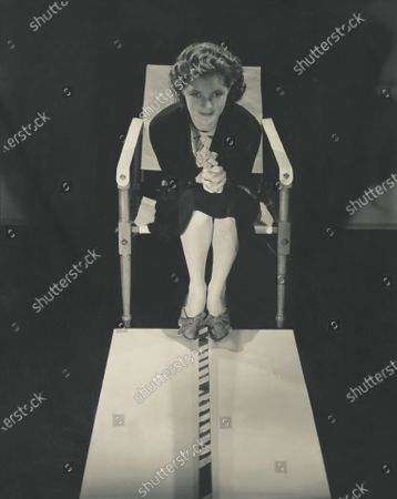 Actress Linda Watkins wearing a dark suit and suede shoes; sitting in a director's chair, leaning forward, hands clasped; from the play, June Moon. Linda Watkins