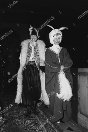 Baron Eric de Rothschild and Lady Jane Willoughby arriving at the Redé Oriental Ball in Paris; he wears a Tartar horseman's costume with fur- lined coat and fur hat, she is wearing a turban with feathers and a caftan. Baron Eric de Rothschild, Lady Jane Willoughby