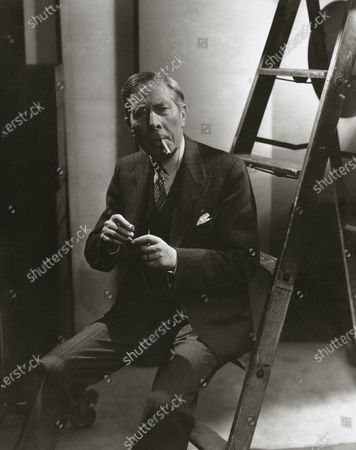 Actor George Arliss sitting on a ladder, lighting his cigarette. George Arliss