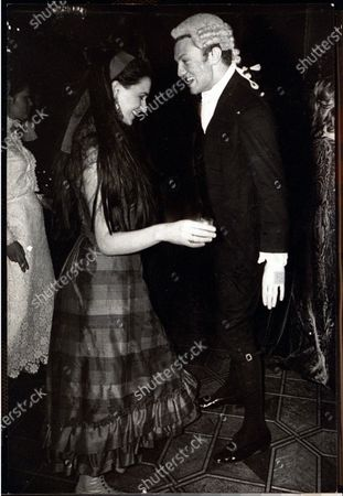 Marina Warner (wearing long flounced dress and holding a drink) dancing with Honorable William Shawcross (wearing white wig and knickers) at costume ball given by the Earl and countess of Longford, at Strawberry Hill, England. Marina Warner, William Shawcross
