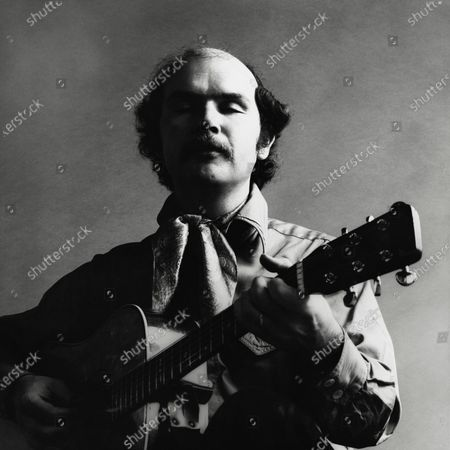 Portrait of Tom Paxton, folk singer, playing a guitar, wearing a scarf tied around his neck. Tom Paxton