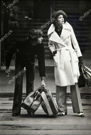 French actor Gérard Falconetti (wearing St. Laurent), picking up Gucci luggage for model Gunilla Lindblad wearing white mohair coat by Henry Friedricks and flared, check pants by Scott Barrie with Van Raalte gloves and Palizzio shoes; Hair by Jean-Louis David. Gerard Falconetti, Gunilla Lindblad