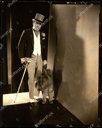 Harvey Ladew, wearing a top hat and carrying a walking stick and with his dog, as Berry Wall, at Elsa Maxwell's masquerade ball at the Ritz-Carlton in New York City. Harvey Ladew