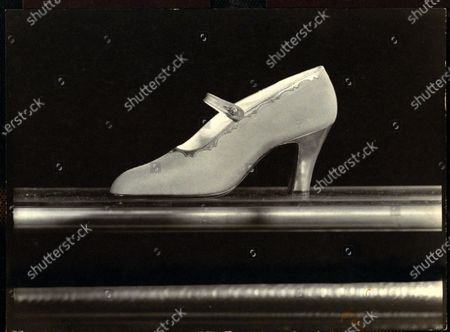Crepe de chine pump with scalloped border and strap fastened with gold rose-shaped button, from Bunting.