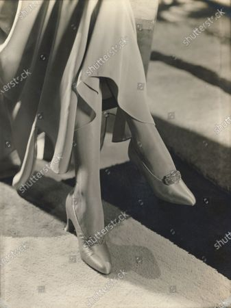 Model wearing satin pumps wtih Louis XV heels and an enamel and rhinestone buckle, from Hellstern, and a long evening dress.