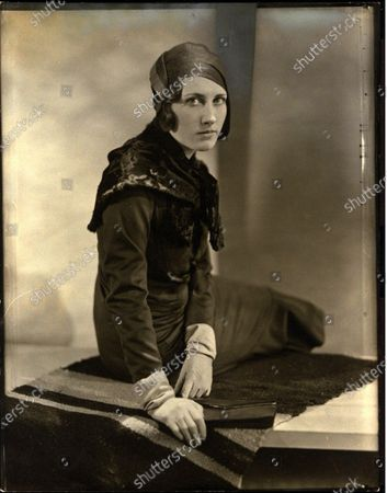 Stock Image of Model wearing 84 straw turban with grosgrain ribbone by Marie-Alphonsine, and a wool dress and a caracul shoulder cape, both by Lucien Lelong.