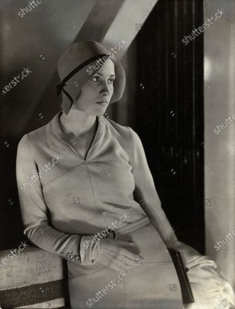Model wearing Rose Descat cloche with ribbon and a tweed dress and jacket, both by Lelong.