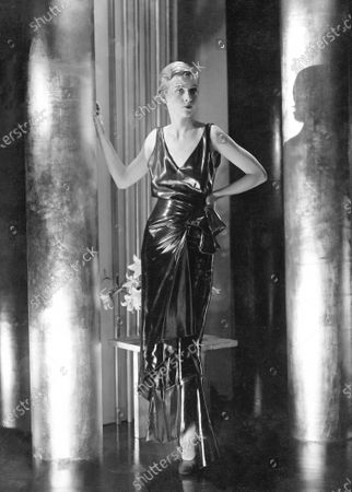 Model Bettina Jones wearing a Schiaparelli Pinafore evening dress of ciré satin with a bow on the side and a low V-neckline which extends to the waist in the back; Model stands between columns with gilt-like finish and low table with vase of flowers behind. Bettina Bolegard