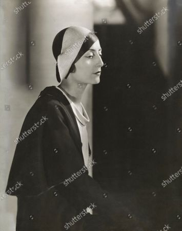 Stock Picture of Madame Simone Demaria wearing Arlequin, a two-tone bicorne, by designer Agnes, dress by Lucile Paray, black crepe jacket with a white crepe de chine top. Simone Demaria