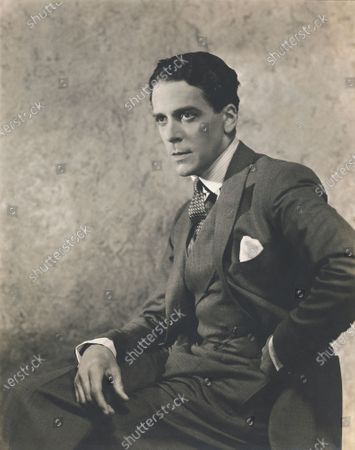 English actor, Jack Buchanan, sitting in profile, with his legs crossed and hand on his hip. Jack Buchanan