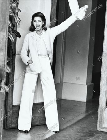 Model Debbie Dickinson, standing with hand in pocket and holding to a curtain, wearing an unlined Chanel cardigan in off-white nubby wool with off-white wool jersey pants and ecru crepe de Chine shirt and cashmere scarf, by Chanel. Debbie Dickinson