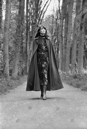 Francoise Hardy, French singer, wearing a Liberty wool challis print floral dress and a long cape, red boots, all by Yves Saint Laurent; she walks on a path in the Bois de Boulogne, in Paris. Francoise Hardy