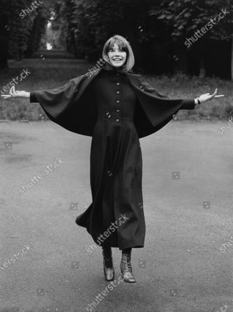 Francoise Hardy, French singer, wearing a coachman's coat with a small cape, lace boots, all by Yves Saint Laurent; she walks with her arms out. Francoise Hardy