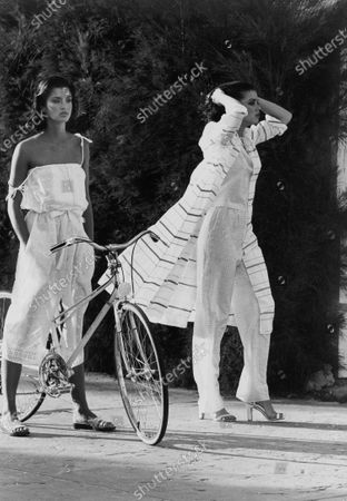 Two models, sisters Janice Dickinson and Debbie Dickinson, at the Boca West Resort, in Florida; left, straddling a bicycle, and wearing a white cotton eyelet top and matching skirt by Betty Hanson & Co.; right, wearing a color-striped crepe de Chine coat and tattersall checked pajamas, by Gloria Vanderbilt. Janice Dickinson, Debbie Dickinson