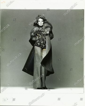 Actress and model Rene Russo wearing an Ungaro ensemble of a long, woven-striped alpaca coat with fox collar, printed challis blazer with matching crepe de chine shirt and wide-leg tweed pants; hairstyle by Jean-Louis David. Rene Russo