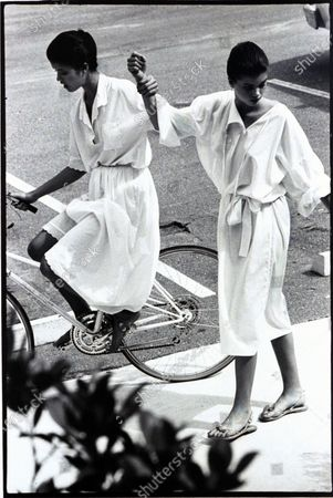 Two models (sisters Janice Dickinson and Debbie Dickinson), at the Boca West Resort, in Florida; Left model riding a bicycle, wearing a white eyelet blouse and matching skirt by Blassport, and holding onto right model in a white cotton kimono-dress, by Scott Barrie. Janice Dickinson, Debbie Dickinson