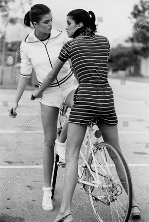 Two models (sisters Janice Dickinson and Debbie Dickinson), straddling a bicycle at the Boca West Resort, in Florida, and wearing ensembles by Ralph Lauren (left to right): white sweater with dark piping, white T-shirt and short shorts; dark cotton knit polo shirt and striped shorts. Janice Dickinson, Debbie Dickinson