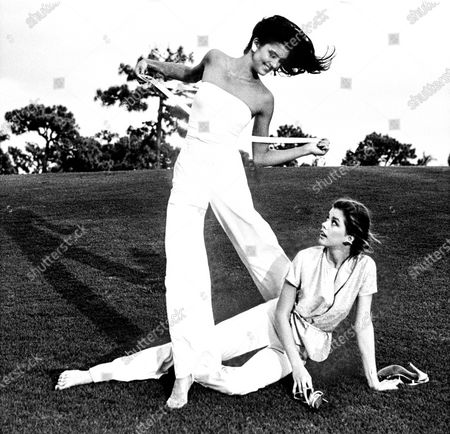 Two models, sisters Janice Dickinson and Debbie Dickinson, on the golf green of the Boca West Resort, in Florida; left model wearing a white strapless wrap top and white pants by John Anthony; right, seated on the grass, wearing a Lurex T-shirt by Blassport, and white jersey pants by Missoni. Janice Dickinson, Debbie Dickinson