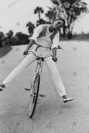 Model Debbie Dickinson, riding a bicycle, and wearing an oversized white cotton T-shirt, dark pencil-striped vest and white pants, by Calvin Klein. Debbie Dickinson