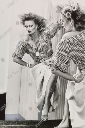 Model, gazing in a wall mirror, with hand on hip and one leg up, and wearing a print peasant blouse and ivory silk pongee full skirt, by Donna Karan for Anne Klein, with a white bracelet and pendant on a chain. Noot Seear