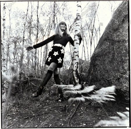 Actress Olga Georges-Picot in the woods, holding a tree, wearing black wool knit miniskirt with huge white stars and long-sleeved tight black knit top, and shiny white belt, all designed by Gino Paoli; Van Raalte black kneesocks; shiny black brogues by Walter Steiger for Pancaldi; Hair by Carita. Olga Georges-Picot