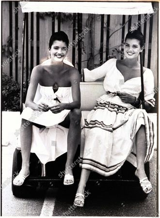 Models, Janice Dickinson and her sister Debbie, sitting on a bench at the Boca West Resort, in Florida, and wearing, from left to right: white cotton strapless dress with a dark knot at chest, by Geoffrey Beene; and white peasant blouse with striped skirt by Oscar de la Renta. Janice Dickinson, Debbie Dickinson