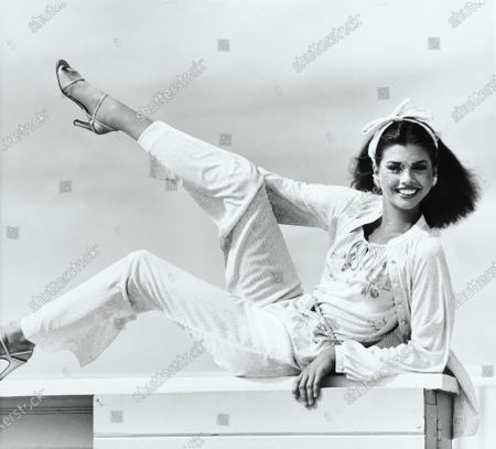 Model Debbie Dickinson, reclining on a ledge with her right leg up in the air, smiling, and wearing a bark-patterned jersey cardigan, rose-print camisole and matching narrow pants, by Leslie Fay, with a hair ribbon tied in a bow. Debbie Dickinson