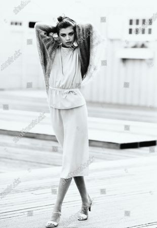 Model Debbie Dickinson, standing on a wooden deck with arms raised behind her head, and wearing a light silk blouse and matching skirt by McMullen. Debbie Dickinson