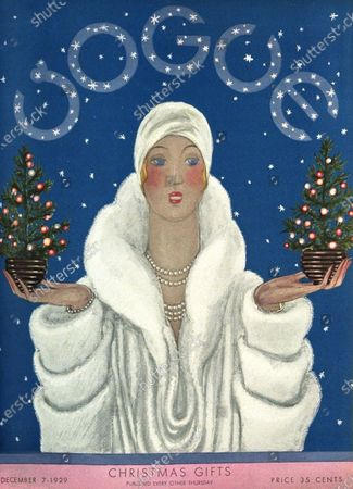 Vogue December 07, 1929 Magazine Cover featuring: Vogue cover with coverlines: Christmas Gifts; illustration of a woman in a white fur coat and a white turban style hat, holding a small potted and decorated Christmas tree in each hand, the word Vogue formed as part of the starry sky in the background.