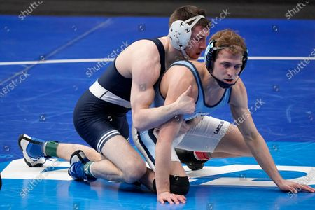 North Carolina's Zachary Sherman, right, takes on Penn State's Nick Lee during their 141-pound match in the quarterfinal round of the NCAA wrestling championships, in St. Louis
